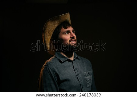 Cowboy in Studio Lighting smiling at light silly - stock photo
