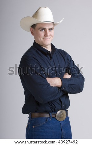 Cowboy in studio with his saddle, chaps, and bridle - stock photo