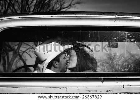 Cowboy kissing woman in pickup truck - stock photo