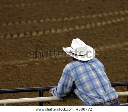 Cowboy leaning on fence watching action in arena - room for text - stock photo