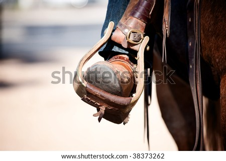 Cowboy leg and foot in stirrup on horse - stock photo