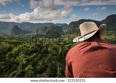Cowboy looking over Vinales Valley landscape with mogotes in Cuba - stock photo