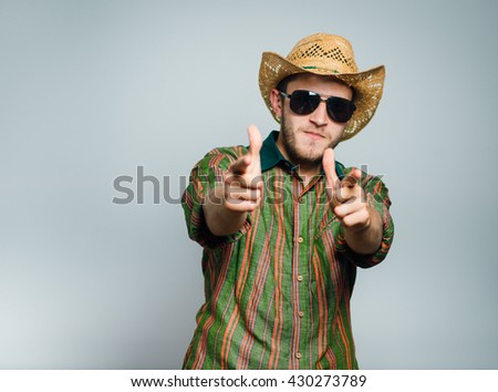 cowboy man points a finger at you, wearing sunglasses and a hat, isolated on gray background - stock photo