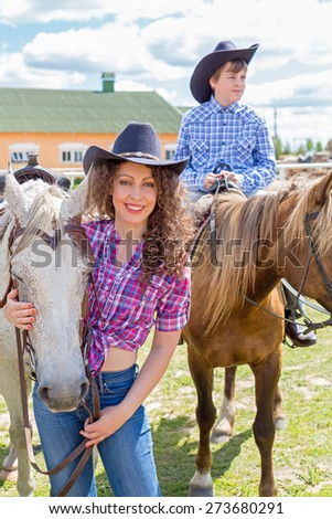 cowboy mother and son with horses - stock photo