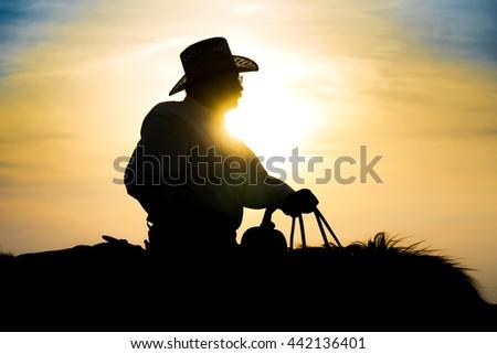 Cowboy on Horseback at Sunset in the Flint Hills of Kansas - stock photo