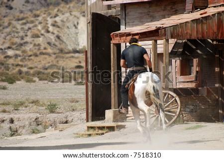 Cowboy on horseback riding away - stock photo