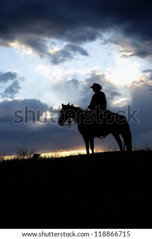 Cowboy,on horseback, silhouetted against dawn sky - stock photo