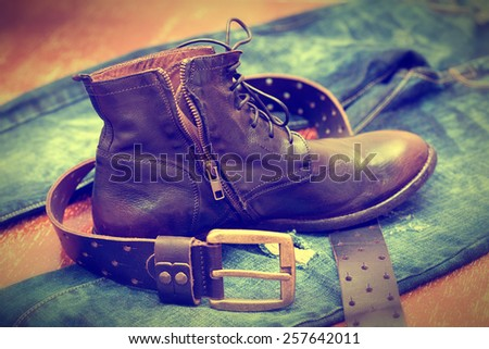 Cowboy outfit - blue jeans, high leather boots, leather belt with buckle - stock photo