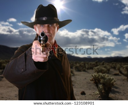 Cowboy pointing gun with selective focus on gun against desert background - stock photo