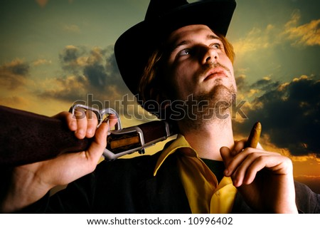 Cowboy relaxing in the last moments before the sun sets. - stock photo