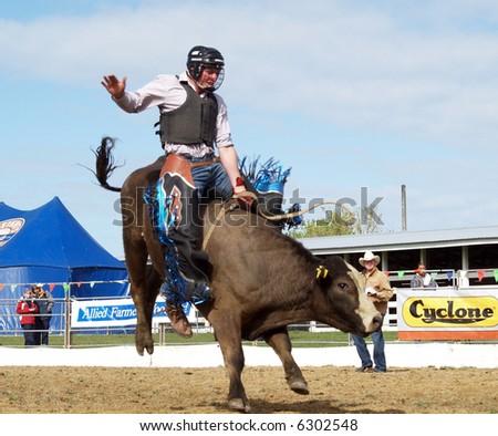 cowboy riding a bucking bull - stock photo
