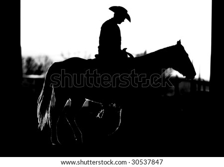 Cowboy riding a horse in silhouette (BW). - stock photo