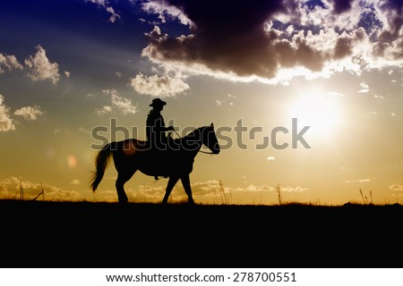 Cowboy riding his horse along the range on a colorful afternoon sunset - stock photo