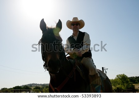Cowboy riding his horse with the sky in the background - stock photo