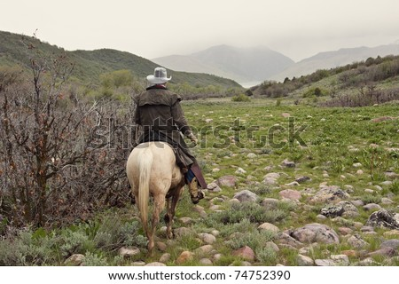 cowboy riding white horse in stormy weather - stock photo