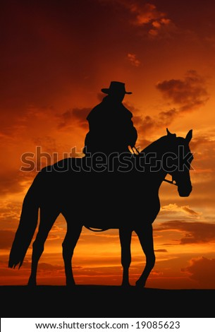 cowboy silhouette in sunrise - stock photo