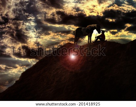 Cowboy silhouette on horse at sunset - stock photo