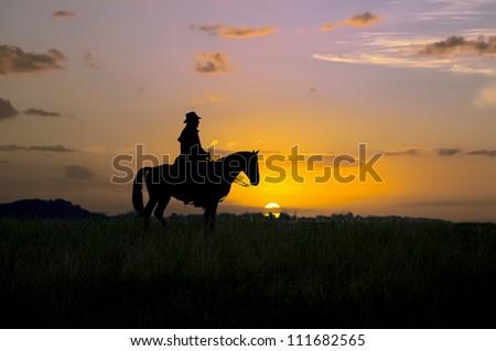 Cowboy sitting on his horse at sunrise. Montana - stock photo