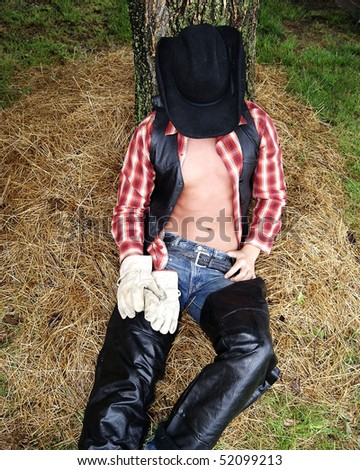 Cowboy sleeping under tree - stock photo