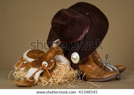 Cowboy theme props on khaki background fabric - stock photo