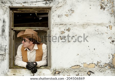 Cowboy Through Old Window - stock photo