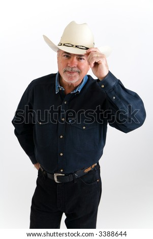 Cowboy tipping his hat, saying hello and smiling - stock photo