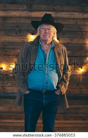 Cowboy wearing coat and jeans shirt standing in front of wooden wall with light bulbs. - stock photo