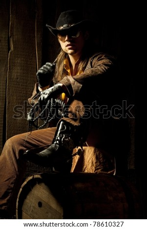 Cowboy with Black Leather Flogging Whip in his hand against wooden background - stock photo