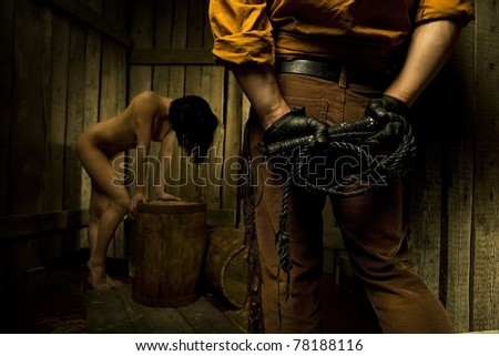 Cowboy with  Black Leather Flogging Whip in his hand and naked bondwoman against wooden background - stock photo