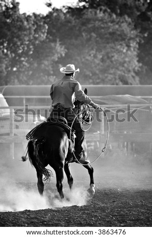 cowboy with lasso on horse at a rodeo, converted with added grain - stock photo
