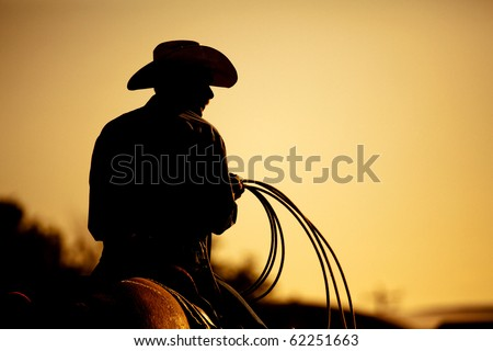 cowboy with lasso silhouette at small-town rodeo. Buyers note: image contains added grain to enhance theme of image. - stock photo