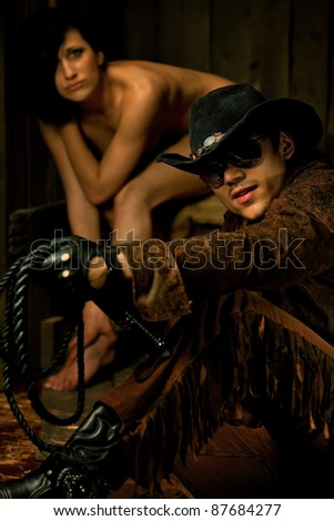 Cowboy with scared bondwoman against wooden background - stock photo