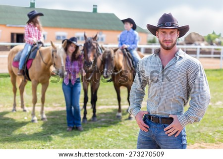 cowboy with wife and children on horses - stock photo