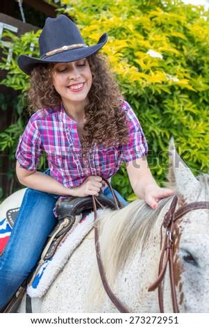 cowboy woman on a horse closeup - stock photo