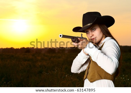 Cowboy woman with a gun in a sunset time. - stock photo