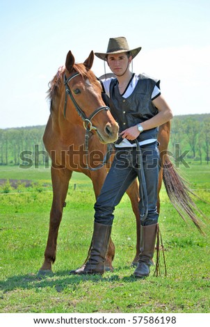 cowboy - young and attractive man riding brown horse