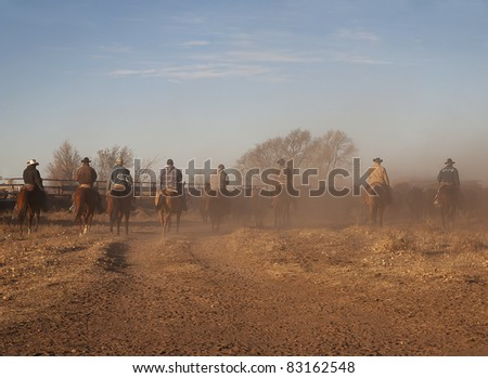 Cowboys on horse back rounding up the cattle on a ranch in Colorado - stock photo