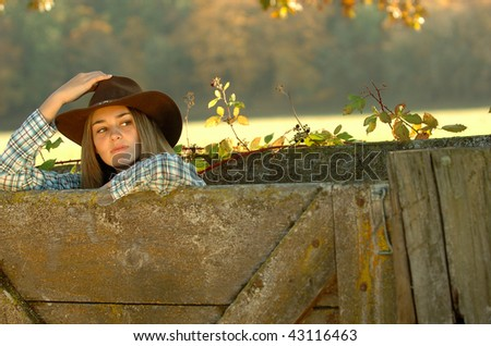 cowgirl and fence - stock photo