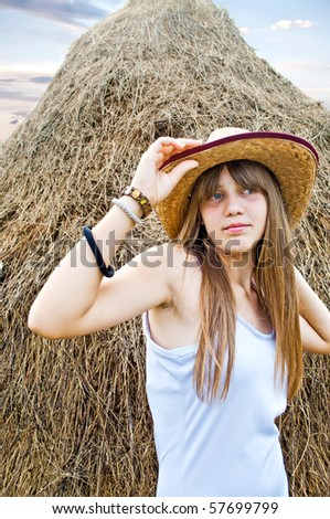 Cowgirl and haystack - stock photo