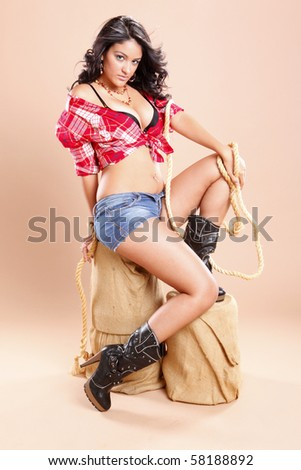 Cowgirl and rope on sisal stool - stock photo