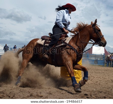 Cowgirl competing in the barrel race - stock photo