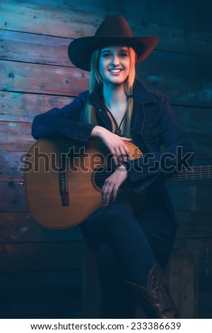 Cowgirl country singer with acoustic guitar. Wearing blue jeans and brown hat. In front of wooden wall. - stock photo