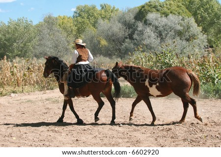 Cowgirl dressed in traditional attire leads paint horse down dusty road in New Mexico - stock photo