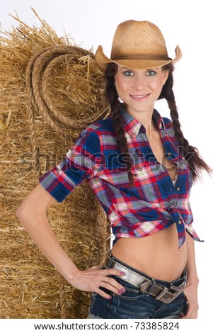 Cowgirl Female Standing Hands on Hips Leaning on Hay Bale Attractive Woman - stock photo