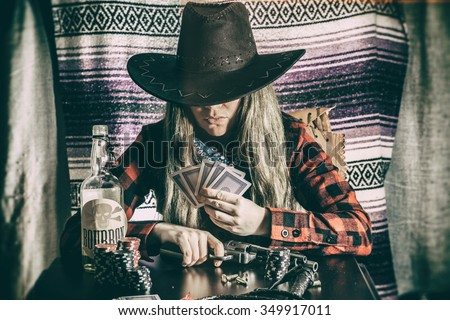Cowgirl Gunslinger Poker Cards. Old west cowgirl gunslinger sitting at table player poker with peacemaker gun, edited in vintage film style. - stock photo