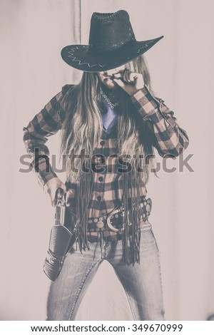 Cowgirl Gunslinger Western Stance. Old west cowgirl gunslinger standing like a cowboy with peacemaker gun and smoking, edited in vintage film style. - stock photo