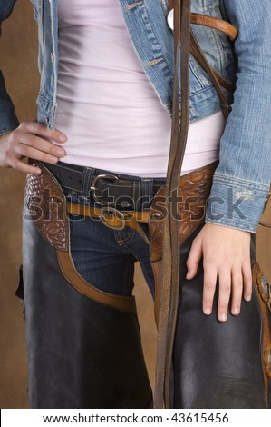 Cowgirl holding bridle and wearing chaps