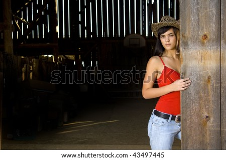 Cowgirl in barn doorway with hat and tank top - stock photo