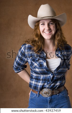 Cowgirl in studio with hat, jeans, and chaps - stock photo