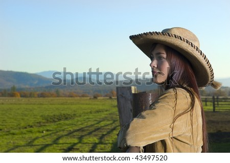 Cowgirl looking over fence with a Fall background with copy space - stock photo